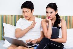 Olyckliga asiatiska par som har frågor som surfar internet Royaltyfria Bilder