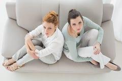 Olyckliga kvinnliga vänner som inte talar efter argument på soffan Arkivfoto