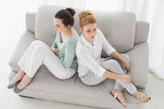 Olyckliga kvinnliga vänner som inte talar efter argument på soffan Royaltyfri Foto