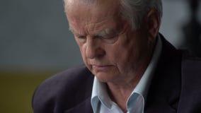 Olyckliga ledsna och besvärade äldre manblickar på en preventivpiller och att gå för att ta den arkivfilmer