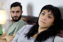 Olyckliga par i säng som slåss den ledsna closeupen royaltyfria bilder