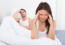 Olyckliga par på säng Royaltyfria Foton
