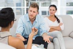 Olyckliga par på terapiperioden med mannen som talar till terapeuten Royaltyfria Bilder