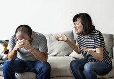 Olyckliga par som argumenterar på soffan Royaltyfri Foto