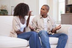 Olyckliga par som argumenterar på soffan Arkivbild