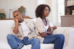 Olyckliga par som argumenterar på soffan Royaltyfri Fotografi