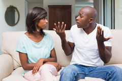 Olyckliga par som har ett argument på soffan Royaltyfri Foto