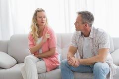Olyckliga par som har ett argument på soffan Arkivfoto