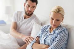Olyckliga par som har konflikt i säng hemma Royaltyfri Fotografi