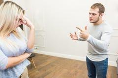 Olyckliga unga par som gr?lar i vardagsrummet arkivfoton