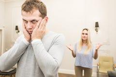 Olyckliga unga par som gr?lar i vardagsrummet arkivfoto