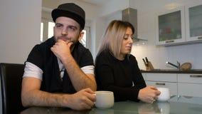 Olyckliga upprivna par som har morgonkaffe som inte till varandra talar efter en kamp arkivfilmer