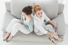 Olyckliga vänner som inte talar efter argument på soffan Fotografering för Bildbyråer