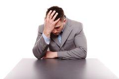 Olyckligt affärsmansammanträde på skrivbordet med handen på huvudet Fotografering för Bildbyråer