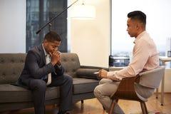 Olyckligt affärsmanSitting On Couch möte med den manliga rådgivaren i regeringsställning royaltyfri bild