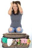 Olyckligt frustrerat attraktivt sammanträde för ung kvinna på en flödande över resväska Arkivfoto