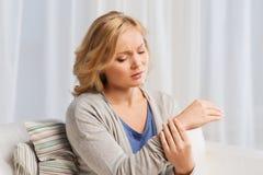 Olyckligt kvinnalidande från smärtar i hand hemma Royaltyfria Bilder