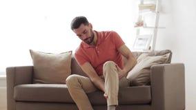Olyckligt manlidande från smärtar i ben hemma stock video