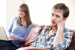 Olyckligt mansammanträde på Sofa As Partner Uses Computer Royaltyfria Bilder