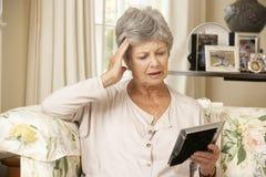Olyckligt pensionerat högt kvinnasammanträde på det Sofa At Home Looking At fotografiet royaltyfria bilder