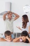 Olyckligt syskon som sitter i kök med deras föräldrar som är a Arkivbilder