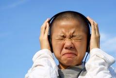 Olyckligt teen med hörlurar arkivbild