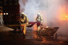 olycksbrandmän räddar offer Fotografering för Bildbyråer