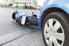 Olycksmotorcykel och bilar på vägen Arkivfoton