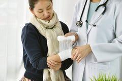 Olycksskadahand, asiatisk kvinnlig doktor med stetoskopet som f?rbinder handen av patienten i sjukhus royaltyfria bilder