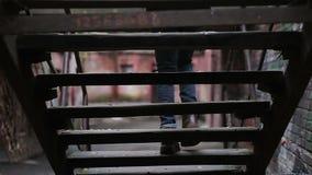 Olydig tonåringvandring i den öde gamla gatan, hoppande over grupper för student stock video