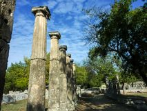 Pillars of marble against the blue sky and cloudsÑŽ Olympia, Peloponnes, Greece. Olympia, Greece - October 31, 2017: Pillars of marble against a blue sky and royalty free stock photography