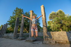 Olympia Greece. A smiling and happy tourist jumps between the columns of the palaestra, where the athletes were training for the Olympic Games. Ancient Olympia Royalty Free Stock Photo