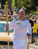 Olympic 2012 Torch Relay Runner. A man running with the 2012 Olympics Torch in Connah's Quay, North Wales Stock Image