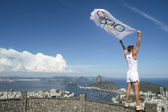 Olympic Athlete with Flag Rio de Janeiro. RIO DE JANEIRO, BRAZIL - MARCH 05, 2015: Athlete stands holding Olympic flag above city skyline view of Sugarloaf stock image