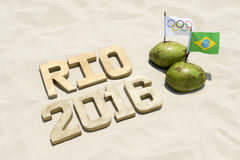 Olympic and Brazilian Flags in Coconuts with 2016 Rio. RIO DE JANEIRO, BRAZIL - FEBRUARY 12, 2015: An Olympic and Brazilian flag fly in coconuts next to a Rio Royalty Free Stock Image