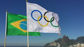 Olympic and Brazilian Flags Flying Rio de Janeiro Brazil. RIO DE JANEIRO, BRAZIL - FEBRUARY 12, 2015: An Olympic and Brazilian flag fly together in slow motion stock video footage