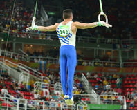 Olympic champion Eleftherios Petrounias of Greece competes at the Men`s Rings Final on artistic gymnastics competition at Rio 2016. RIO DE JANEIRO, BRAZIL Royalty Free Stock Photography