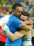 Olympic champion Eleftherios Petrounias of Greece R with his coach after Men`s Rings Final on artistic gymnastics competition Stock Photos