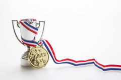 Olympic champion, gold medal winner. Gold medal with ribbon wrapped around a silver trophy stock image