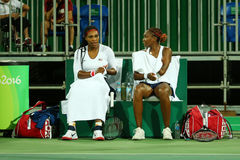 Olympic champions Serena Williams (L) and Venus Willams of United States in action during doubles first round match Royalty Free Stock Images