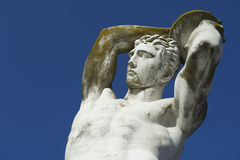 Olympic Discus Thrower Old Marble Statue. Ancient marble statue of muscular Olympic athlete discus thrower throwing a discus against bright blue sky Royalty Free Stock Images