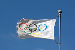 Olympic flag against a blue sky in sunlight. Olympic flag against a blue sky in the sunshine Royalty Free Stock Photos