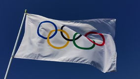 Olympic Flag Fluttering in Bright Blue Sky stock footage