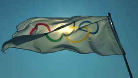 Olympic Flag Fluttering in Bright Blue Sky stock video