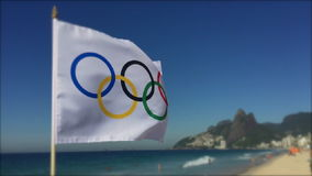 Olympic Flag Flying Rio de Janeiro Brazil. RIO DE JANEIRO, BRAZIL - FEBRUARY 12, 2015: An Olympic flag flies in slow motion with selective focus above Ipanema stock video