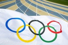 Olympic Flag Waving at Running Track. NEW YORK CITY, USA - AUGUST 20, 2015: Olympic flag waves over the lanes of a blue and tan running track royalty free stock images