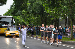 Olympic flame carried by the torchbearer Royalty Free Stock Images