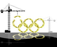 Olympic games Construction. Olympic gold rings under construction by crane silhouettes. Reflection below Royalty Free Stock Photography