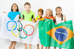 Olympic Games. Rio de Janeiro 2016 Brazil. Children holding a flag of five rings symbol of Olympic Games and Brazil flag. Rio de Janeiro 2016 Brazil. Happy fans Royalty Free Stock Photos