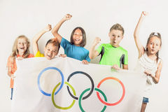Olympic Games. Rio de Janeiro 2016 Brazil. Group of children holding a flag of five rings symbol of the Olympic Games. Rio de Janeiro 2016 Brazil. Happy fans of Stock Image